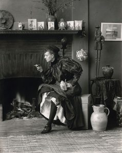 "Frances Benjamin Johnston's Self-Portrait (as ""New Woman""), a full-length self-portrait of her seated in front of fireplace, facing left, holding cigarette in one hand and a beer stein in the other, in her Washington, D.C. studio"