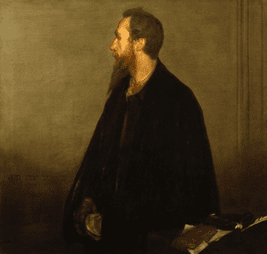 Charles De Sousy Ricketts is wearing a black cloak, only being able to see half his face and red beard that comes down to his collar bones. He is looking to his right, with hands holding one another under his cloak, beside a table.