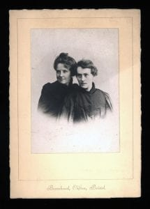 portrait of two women dressed in black. Woman on the left wears her hair up on her head, woman on the right has short hair