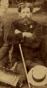 Captured image of middle-aged man (Geddes) sitting outdoors with arms crossed. There is a white hat placed at the bottom right of the image, below Patrick Geddes. Image is in sepia-tinted, light brown colour.