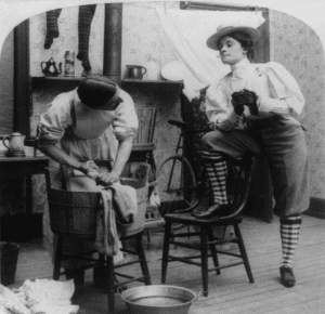 black and white photo of a woman standing with leg up on chair as a man does laundry next to her