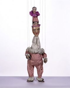 A marionette with red and white striped clothing and a long neck with three faces on top of each other.