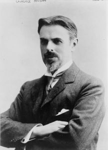 A black and white half-length photographic portrait of Laurence Housman, turned to the right with his arms crossed.
