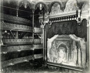 Grey-scale image of the stage and the left balcony seats of the Alhambra Theatre